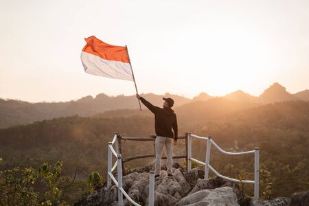 asian male with indonesian flag celebrating independence day Фото со стока