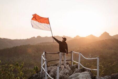Varón asiático con bandera de Indonesia celebrando el día de la independencia Foto de archivo