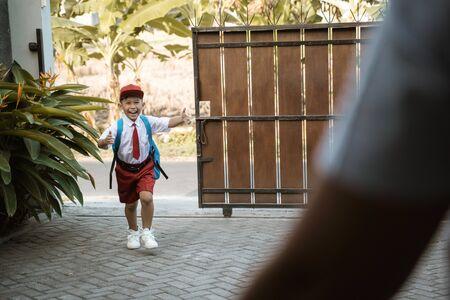 elementary student wearing school uniform running toward his parent Reklamní fotografie