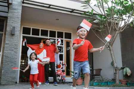 family celebrating indonesian independence day together carrying flag Stok Fotoğraf