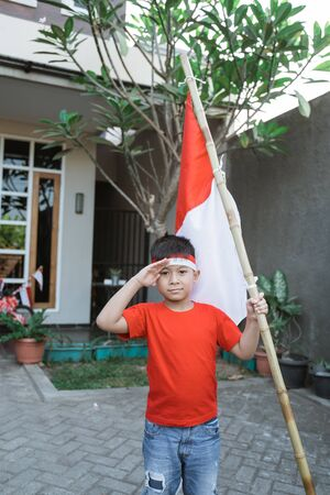 asian kid saluting while holding indonesia flag