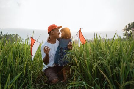indonesian kid with father play with national flag
