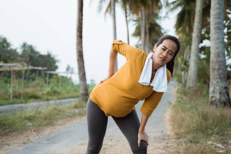 pregnant woman back pain during exercising outdoor Stockfoto