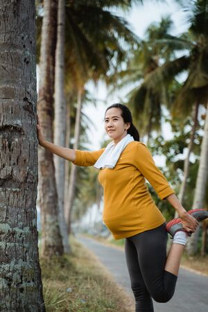 pregnant woman stretch her leg during exercising outdoor Stock fotó