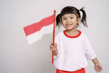 asian toddler with indonesian flag smiling to camera