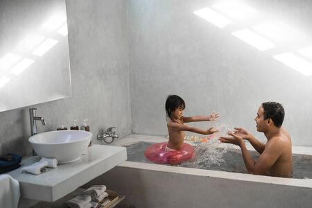 little girl with her father playing water on the bathtub