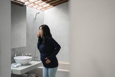 zwangere vrouw voelt zich misselijk in de badkamer Stockfoto