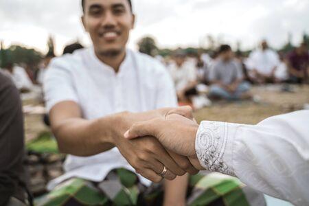 Asian men shake hands after Eid prayer