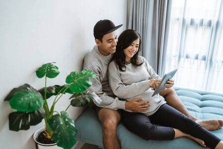 happiness of couples holding the wifes pregnant stomach while using digital tablet