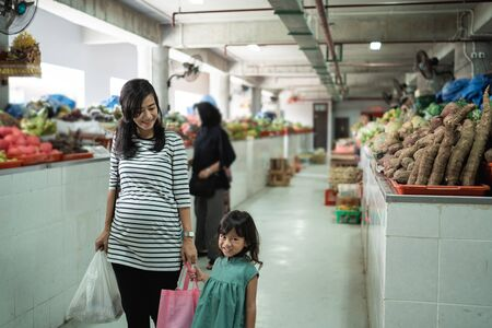 little girls stand smiling with her mother while shopping
