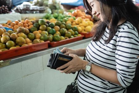 pregnant asian woman take money out of his wallet to pay for goods