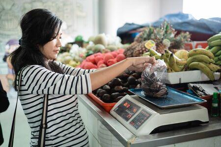 femme asiatique enceinte peser les articles achetés Banque d'images