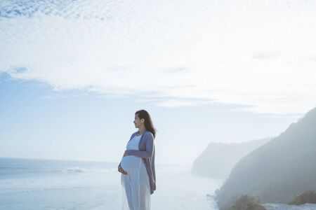 beautiful pregnant woman standing on the beach Banque d'images