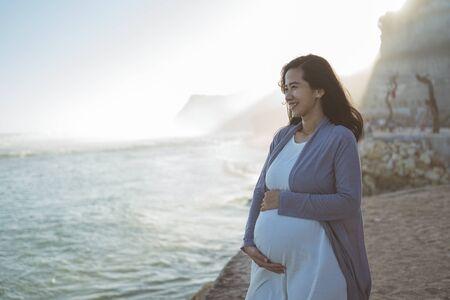 hermosa mujer embarazada de pie en la playa Foto de archivo