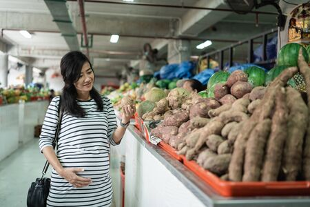 pregnant asian young woman hold items to be purchased Stok Fotoğraf
