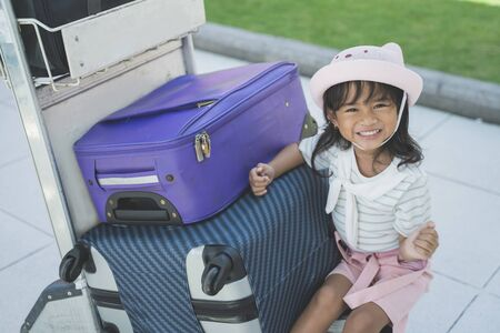 alone little girl sitting beside a suitcase at an airport