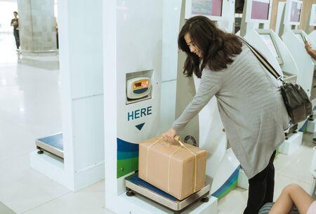 Asian woman take the cardboard on the luggage scale