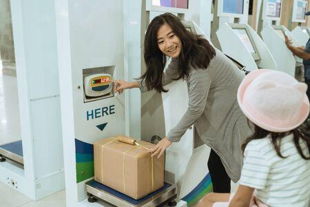 Asian woman put the cardboard on the luggage scale 版權商用圖片