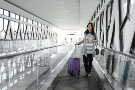 asian pregnant woman standing pulling suitcase Banque d'images - 127833043
