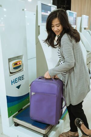 Asian woman put the suitcase on the luggage scale 版權商用圖片