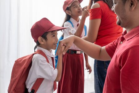student kiss his parents hand before going to school Stock Photo