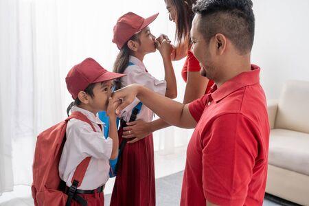lo studente bacia la mano dei suoi genitori prima di andare a scuola