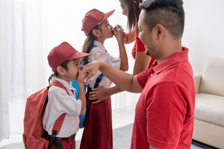 Schüler küsst die Hand seiner Eltern, bevor er zur Schule geht