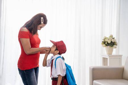 kid kissing mothers hand while shaking hand Standard-Bild