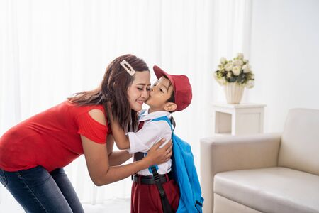 son kiss his mother on cheek before going to school Stok Fotoğraf - 127832836