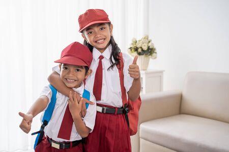estudiante de primaria con uniforme escolar mostrando los pulgares para arriba