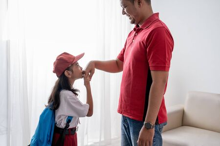 asian kid kiss her fathers hand before going to school