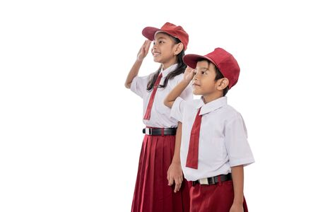 elementary student wearing uniform giving salute to indonesia flag