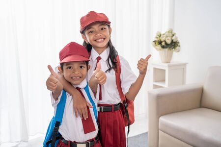 primary student wearing school uniform showing thumbs up