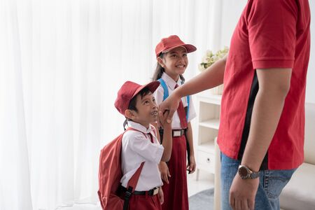 asian kid kiss their fathers hand before going to school Stok Fotoğraf
