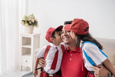 son and daughter kiss father on cheek