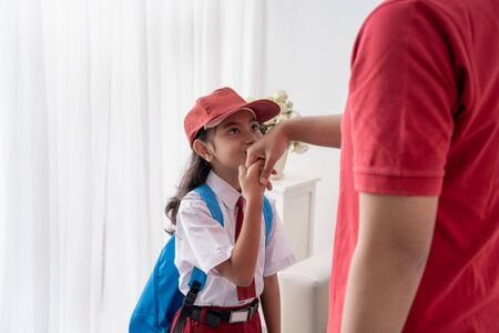 asiatisches Kind küssen die Hand ihres Vaters, bevor sie zur Schule gehen Standard-Bild