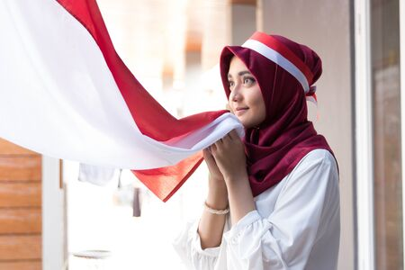 woman with scarf kissing indonesia flag