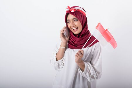 indonesian independence day celebration woman with phone Stock Photo
