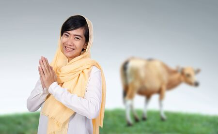 muslim woman with cow for idul adha qurban celebration