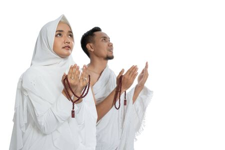 Muslim man and woman praying in white traditional clothes ihram