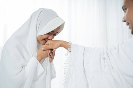 after sholat wife kissing husbands hand wearing white traditional clothes Standard-Bild - 127879243