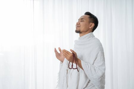 muslim asian man praying with prayer beads Stock fotó - 127879293