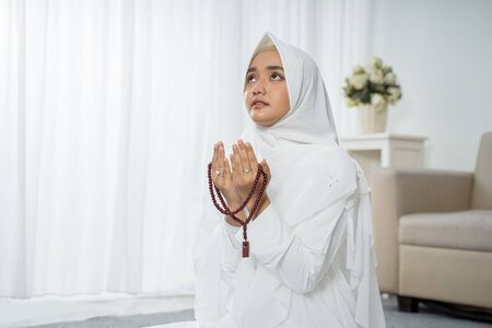 asian young woman praying with Al-Quran and prayer beads