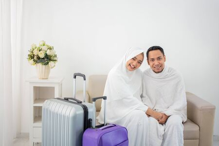 wife and husband in white traditional clothes for Ihram