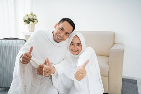 muslim pilgrims wife and husband with thumb up Stock Photo