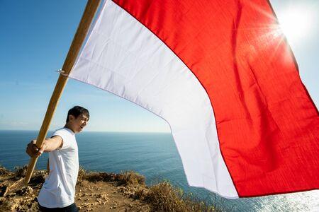 Varón asiático con bandera de Indonesia celebrando el día de la independencia