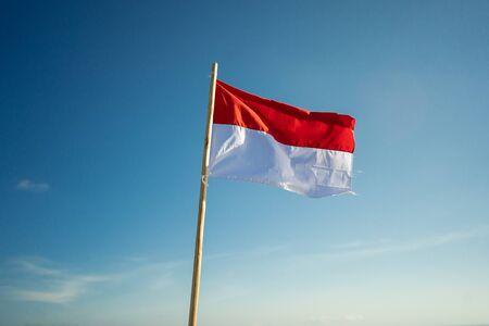 bandera de indonesia bajo un cielo azul Foto de archivo