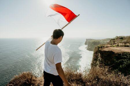 asiatischer Mann mit indonesischer Flagge, der den Unabhängigkeitstag feiert Standard-Bild