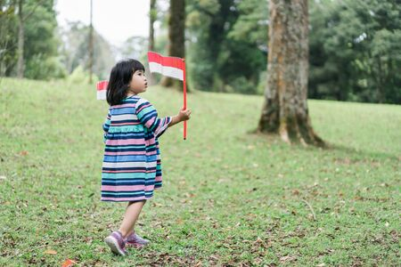 asian girl holding two stick of Indonesian flag