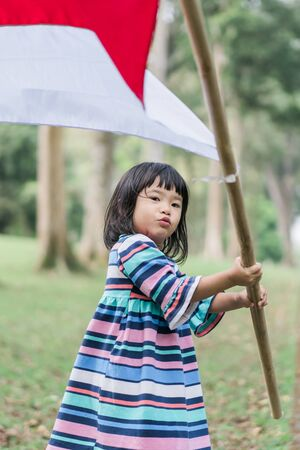 asian little girl flapping Indonesian flag Фото со стока